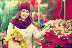 Girl buying floral compositions at Christmas fair Stock Images
