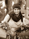 Girl buying floral compositions at Christmas fair Royalty Free Stock Photography