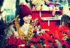 Girl buying floral compositions at Christmas market Royalty Free Stock Photography