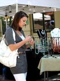 Girl buying jewelry. A teenage girl looking at gemstone necklaces at the market Royalty Free Stock Photography
