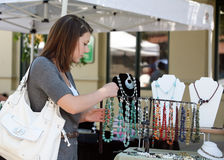 Girl buying jewelry. A teenage girl looking at gemstone necklaces at the market Stock Photos