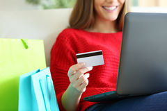 Girl buying on line with credit card. Close up of a girl hand holding a credit card and buying on line with a laptop and shopping bags beside Royalty Free Stock Photography