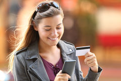Girl buying on line on the street. Portrait of a happy shopper buying on line with a smart phone and credit card on the street stock images