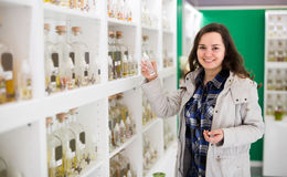 Girl buying perfume in fragrance boutique. Cheerful smiling young brunette choosing perfume in fragrance boutique Royalty Free Stock Photo