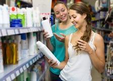 Girl buying shampoo. Happy european girl buying shampoo in shopping mall stock photos