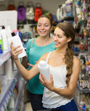 Girl buying shampoo Royalty Free Stock Image