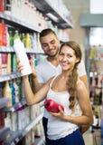 Girl buying shampoo Stock Photos