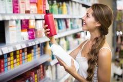 Girl buying shampoo Royalty Free Stock Photos