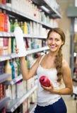 Girl buying shampoo Royalty Free Stock Photo