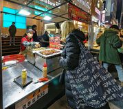 Girl buying street food in Myeongdong street market Seoul Stock Photo