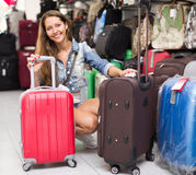 Girl buying suitcase in store Stock Images