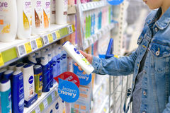 Girl buys Nivea cosmetics. Nowy Sacz, Poland - March 29, 2017:  Young woman in front of aisle with a variety of personal care  products of Nivea Company in a Royalty Free Stock Photography