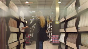 Girl buys a wallpaper in a building store stock video footage