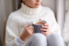 Girl with cacao mug looking at home window. Hot drinks and people concept - beautiful girl in winter sweater with cacao mug sitting at home window Royalty Free Stock Photos