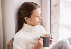 Girl with cacao mug sitting at home window Royalty Free Stock Photography