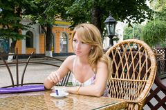 Girl is in a cafe. Young white-headed girl in a cafe with the cup of coffee Stock Image