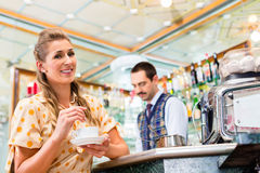 Girl in cafe or bar stirring in coffee cup, barista in back Royalty Free Stock Photography