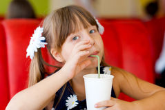 Girl in a cafe with a cocktail. Little girl in a cafe with a glass of cocktail with a straw Royalty Free Stock Photo