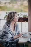 Girl in a cafe with cup of coffee. Girl sitting in a cafe wrapped in blanket and drinking coffee Royalty Free Stock Photos