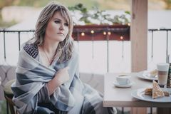 Girl in a cafe with cup of coffee. Girl sitting in a cafe wrapped in blanket and drinking coffee Stock Photography