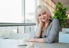 Girl in cafe drinks coffee Stock Photography