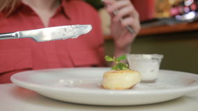 The girl in the cafe eating cheese pancakes with sour cream fork and knife. stock footage