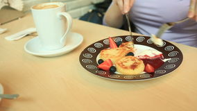 A girl in a cafe eats cheese pancakes with sour cream jam and fresh berries with a knife and fork stock footage