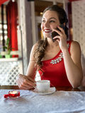 The girl in the cafe. The girBeautiful girl in a red dress in a cafe talking on the phonel in the cafe Stock Image