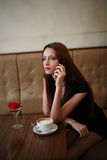 Girl in cafe. Haired girl sitting at table in cafe royalty free stock images