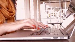 The girl in cafe. Hands touch typing on a laptop keyboard. In the office stock video