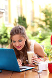 Girl in a cafe with her laptop Stock Photography