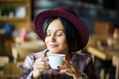 Girl in Cafe holding cup of hot coffee in hand, smiling Royalty Free Stock Photos