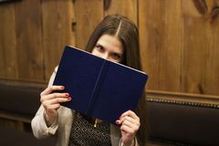 Girl in a cafe holds a blue book near the eyes stock photography
