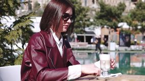 The girl in the cafe, Near a Pool. a beautiful young woman in cafe Drinking Coffee latte under sun light at sunny day. stock video footage
