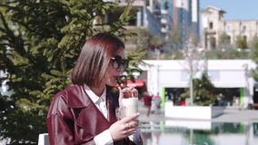 The girl in the cafe, Near a Pool. a beautiful young woman in cafe Drinking Coffee latte under sun light at sunny day. stock footage