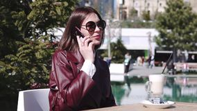 The girl in cafe near the pool. a beautiful young woman in cafe Drinking Coffee latte and using her smartphone under sun stock video