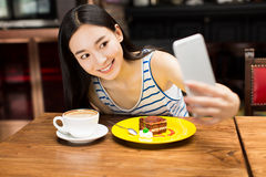 Girl in cafe shop texting on smartphone Royalty Free Stock Images