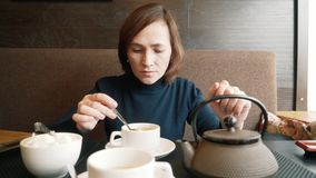 A girl in a cafe stirs sugar in a cup of tea. A woman is drinking green tea in a cafe. stock video
