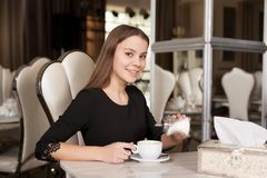The girl in the cafe. Young beautiful girl in black dress sits in a cafe sugar pours and drinks coffee stock images