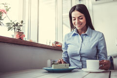 Girl in cafe. The young beautiful girl drinking coffee and dessert eating, sitting in a cafe on the terrace royalty free stock image