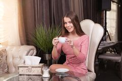 The girl in the cafe. Young beautiful girl in pink dress sits in a cafe looking at the camera and drinks coffee stock photo