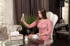 The girl in the cafe. Young beautiful girl in pink dress sits in a cafe taking pictures of himself on the phone and drinks coffee stock image