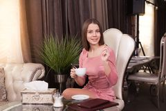 The girl in the cafe. Young beautiful girl in pink dress sits in a cafe and drinks coffee royalty free stock photography