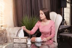 The girl in the cafe. Young beautiful girl in pink dress sits in a cafe and drinks coffee stock images