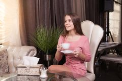 The girl in the cafe. Young beautiful girl in pink dress sits in a cafe looking out the window and drinks coffee stock images