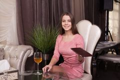 The girl in the cafe. A young beautiful girl in a pink dress sits at a table in a cafe, and gives a folder with a check to the waiter royalty free stock photos