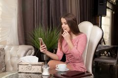 The girl in the cafe. Young beautiful girl in pink dress sits in a cafe uses the phone and drinks coffee royalty free stock photo