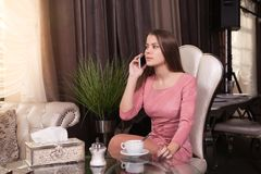 The girl in the cafe. Young beautiful girl in pink dress sits in a cafe uses the phone and drinks coffee royalty free stock photos