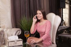 The girl in the cafe. Young beautiful girl in pink dress sits in a cafe uses the phone and drinks wine royalty free stock image