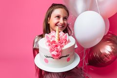 Girl with a cake for a birthday, in the Studio on a pink background, festive mood. Girl with a cake for a birthday, in the Studio on a pink background royalty free stock photos